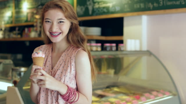 vidéos et rushes de  ms teenage girl holding an ice cream cone in an ice cream shop. - tentation