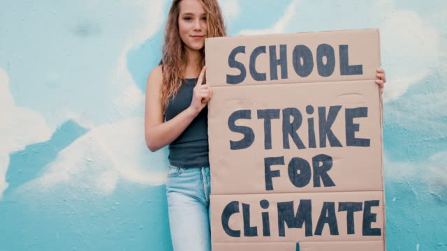 teenage girl holding climate school strike protest sign - demonstrant stock-videos und b-roll-filmmaterial