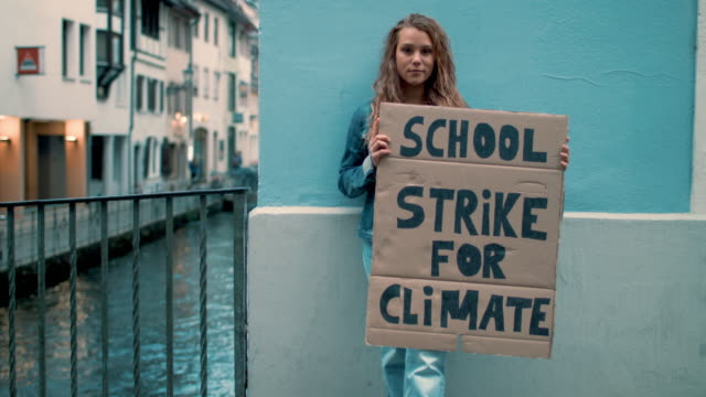 teenage girl holding climate school strike protest sign - klima stock-videos und b-roll-filmmaterial