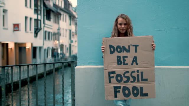 vidéos et rushes de teenage girl holding climate school strike protest sign - rébellion