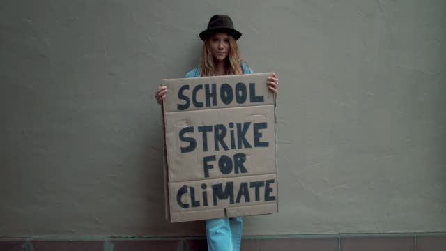 teenage girl holding climate school strike protest sign - aktivist stock-videos und b-roll-filmmaterial