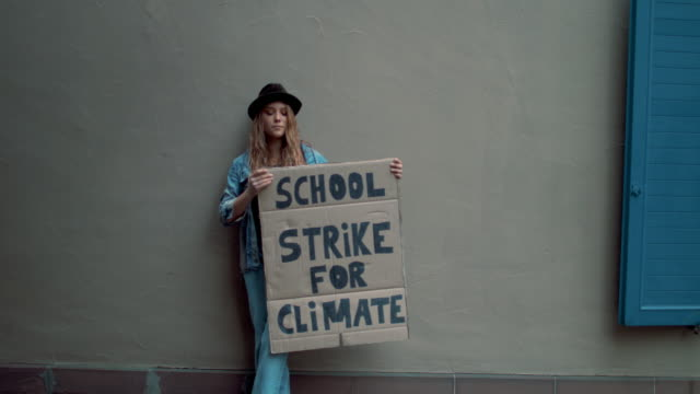 teenage girl holding climate school strike protest sign - generation z stock videos & royalty-free footage