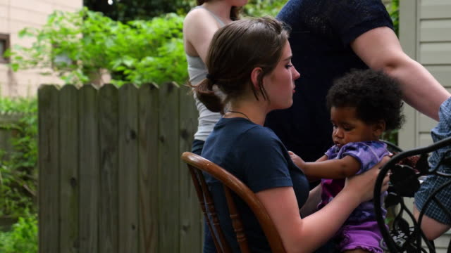 MS PAN Teenage girl holding infant sister in lap during birthday celebration while mom dishes up dessert