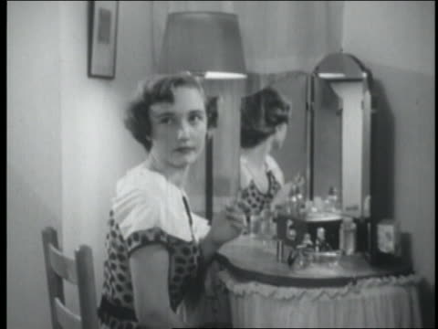 vídeos de stock e filmes b-roll de b/w 1954 teenage girl holding lipstick in front of mirror turns around - 1954