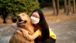 Teenage Girl in air pollution mask hug Golden Retriever