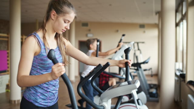 teenage girl in gym exercising on cross trainer - exercise room stock videos & royalty-free footage