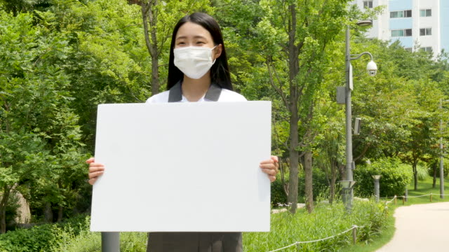 teenage girl in school uniform holding whiteboard as wearing a mask - placard stock videos & royalty-free footage