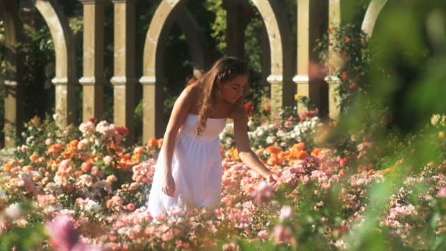 slo mo ws teenage girl (16-17) in summer garden, lehi, utah, usa - maglietta senza maniche video stock e b–roll