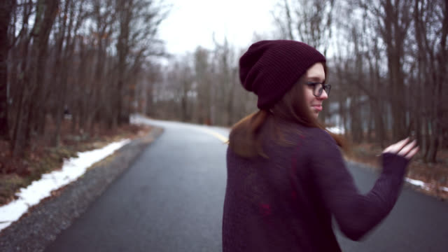 Teenage girl in sweater and hat walking on community road