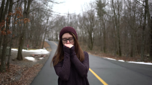 teenage girl in sweater and hat walking on community road - cardigan sweater stock videos & royalty-free footage