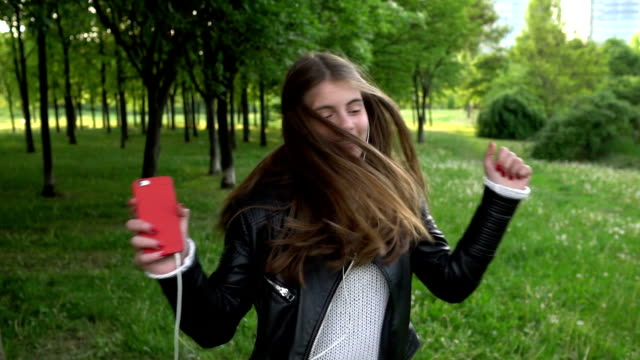 teenage girl in the city park shaking head to the music - mp3 player stock videos & royalty-free footage