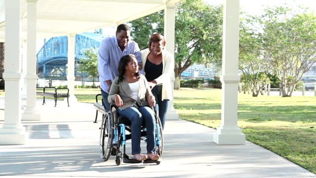 Teenage girl in wheelchair outdoors with parents