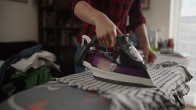 teenage girl ironing clothes at home - iron appliance stock videos & royalty-free footage
