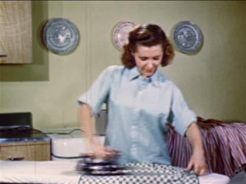 vidéos et rushes de 1952 teenage girl ironing clothes while talking to someone offscreen / industrial - seulement des jeunes filles