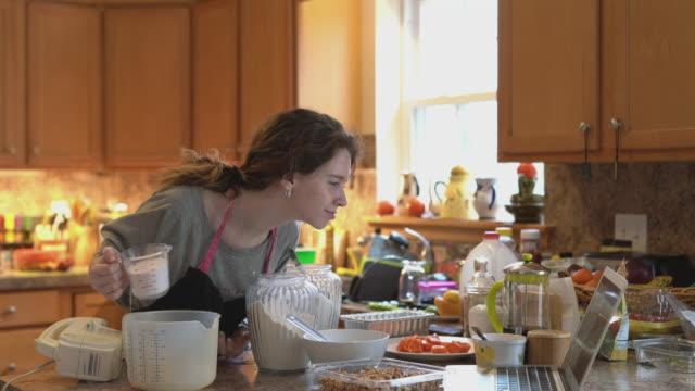 vídeos y material grabado en eventos de stock de la adolescente está horneando, mezclando ingredientes para su masa de pastel y está revisando una receta en una computadora portátil. - 18 19 años
