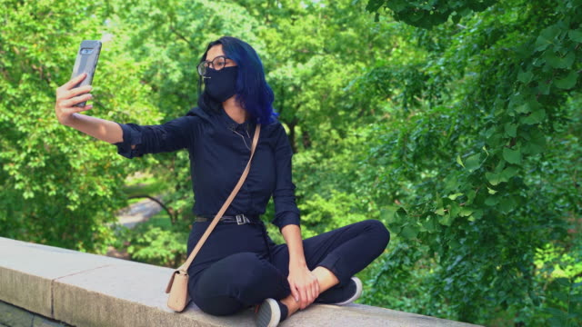 teenage girl is sitting on the stone fence of central park, manhattan, and taking selfies with a smartphone. - 16 17 years stock videos & royalty-free footage