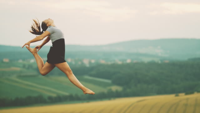vídeos de stock e filmes b-roll de ms teenage girl jumping for joy in rural field - full length