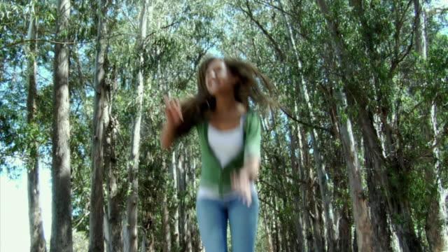 MS, LA, Teenage girl (14-15) jumping in eucalyptus grove, Richmond, California, USA