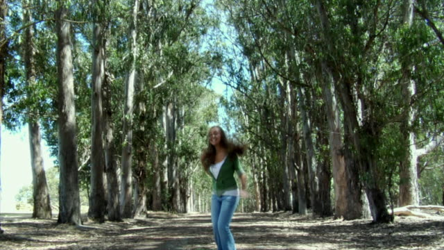 ms, teenage girl (14-15) jumping on dirt track in eucalyptus grove, richmond, california, usa - one teenage girl only stock videos & royalty-free footage