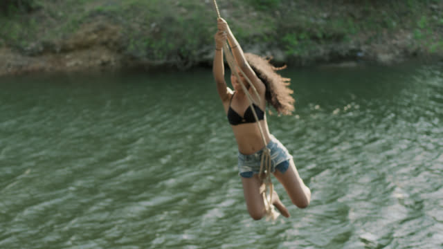 SLO MO. Teenage girl jumps from riverbank with rope swing and falls into water with a big splash.
