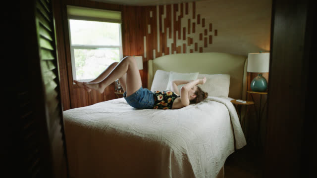 vídeos de stock e filmes b-roll de ws slo mo. teenage girl jumps onto bed in rustic treetop cabin. - cama