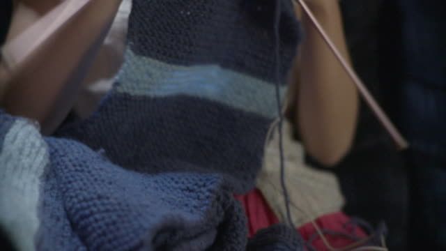 MS TU PAN Teenage girl (16-17) knitting scarf and listening music / Newark, Illinois, USA