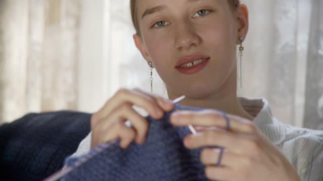 CU TU TD Teenage girl (16-17) knitting scarf and smiling / Newark, Illinois, USA