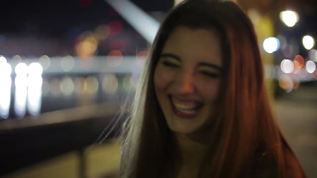 teenage girl laughing at making funny faces outdoors at night - one teenage girl only stock-videos und b-roll-filmmaterial