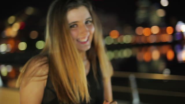 teenage girl laughing outdoors at night portrait - one teenage girl only stock-videos und b-roll-filmmaterial