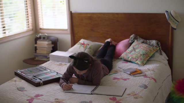 WS teenage girl laying on her bed drawing in her bedroom