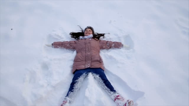 teenage girl laying on snow and making snow-angel