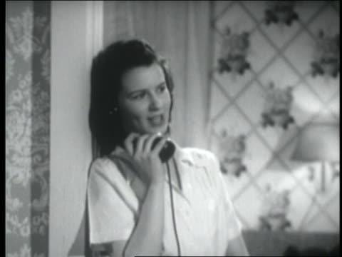 vídeos y material grabado en eventos de stock de b/w 1947 teenage girl leaning against doorway + smiling while talking on telephone - sólo una adolescente