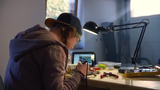 slo mo tonårsflicka lära sig löda genom att titta på en video tutorial i hemmet verkstad - endast en tonårsflicka bildbanksvideor och videomaterial från bakom kulisserna