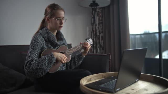 vídeos de stock, filmes e b-roll de adolescente aprendendo a jogar ukulele em casa - ukulele