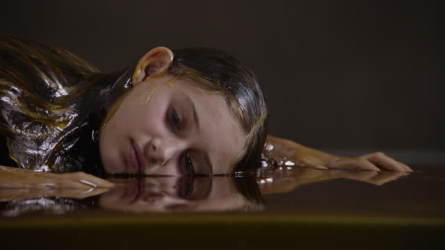 teenage girl lies in honey, close up - one teenage girl only点の映像素材/bロール