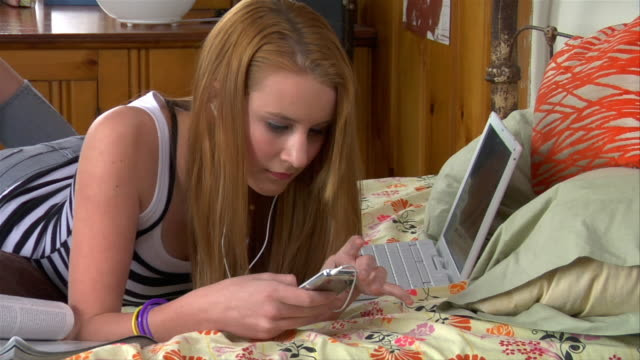 ms teenage girl listening to mp3 player on her bed / brooklyn, new york, usa - mp3 player stock videos & royalty-free footage