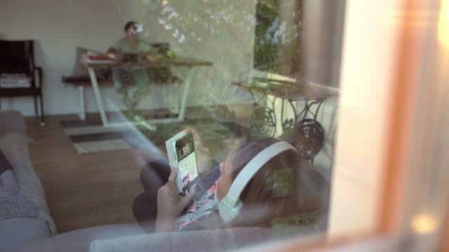 ms-teenage girl musikhören mit kopfhörer und smartphone an wohnzimmerfenster - zuhören stock-videos und b-roll-filmmaterial