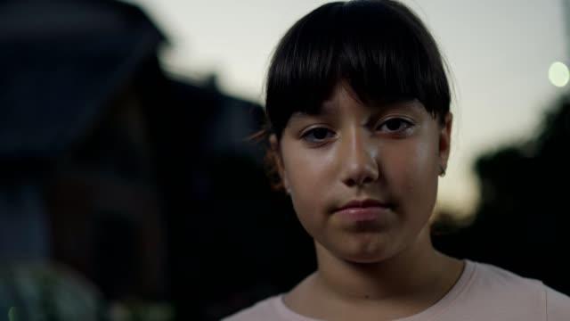 vidéos et rushes de adolescente regardant l'appareil-photo - visage sans expression