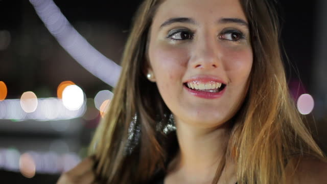 teenage girl looking at city lights and then smiling at camera at night - one teenage girl only stock-videos und b-roll-filmmaterial