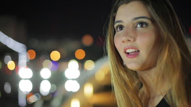 teenage girl looking at night view and then turning to smile at person out of frame - 横目点の映像素材/bロール