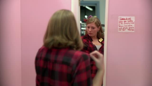 vídeos de stock e filmes b-roll de ms teenage girl (16-17) looking at outfit in mirror / morris, illinois, usa  - cabine de loja