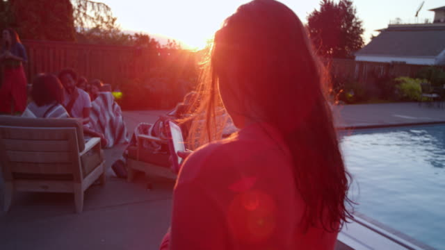 MS Teenage girl looking at smartphone while at pool party in backyard of home on summer evening