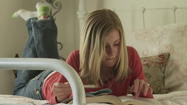 vídeos de stock, filmes e b-roll de ms td teenage girl (14-15) lying on bed, listening music and reading / cedar hills, utah, usa - reclinando