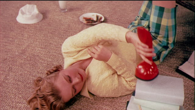 1958 ms zo ha teenage girl lying on floor using ericofon telephone / usa / audio - disco combinatore video stock e b–roll