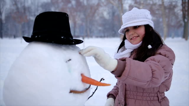 Teenage girl making an snowman in the park