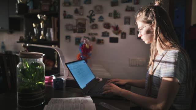 vidéos et rushes de adolescente faisant des devoirs à la maison - élève du secondaire