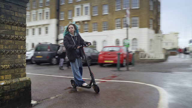teenage girl on e scooter riding round a corner on a rainy winter day - female high school student stock videos & royalty-free footage