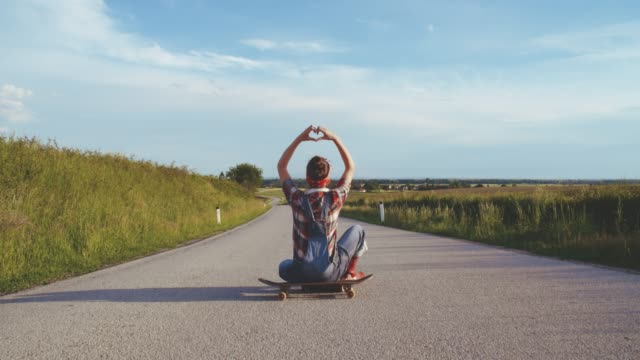 Teenage girl on skateboard forming heart-shape with hands on sunny,rural road,slow motion