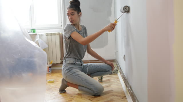 teenage girl painting walls - coda di cavallo video stock e b–roll