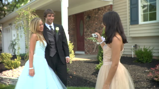 ms, teenage girl (16-17) photographing couple in prom attire in front of house, edison, new jersey, usa - boutonniere stock videos and b-roll footage